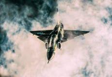 飞行在云彩的军用战机 图库摄影