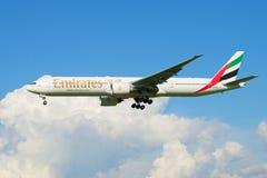 飞行在云彩航空器波音777-300 (A6-EGU)阿联酋国际航空公司中 免版税库存照片