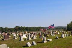 飞行在公墓的美国国旗装饰用花为阵亡将士纪念日在有小山的美国在背景中 免版税库存图片