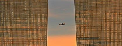 飞行在办公大楼之间的小喷气机引擎耸立 免版税库存图片