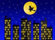 飞行在城市的巫婆的剪影在晚上 库存图片