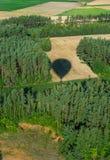 飞行在培养的领域的气球的阴影以无云的天空为目的 免版税库存图片