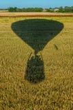 飞行在培养的领域的气球的阴影以无云的天空为目的 库存图片