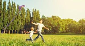 飞行在夏天自然的爸爸和儿子孩子一只风筝 免版税库存图片