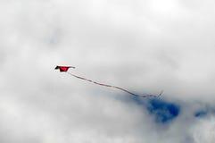 飞行在多云天空的一只风筝 免版税库存照片