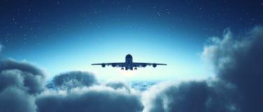 飞行在多云天空的飞机 库存照片