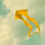 飞行在多云天空的黄色风筝 减速火箭的样式 (被定调子的照片 ) 免版税库存照片