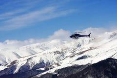 飞行在多雪的山的直升机 库存照片