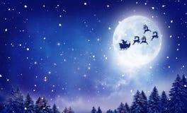 飞行在多雪的风景的圣诞老人和他的雪橇 免版税库存照片