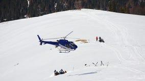 飞行在多雪的滑雪倾斜的直升机 图库摄影