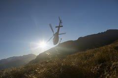 飞行在太阳前面的小山的直升机 免版税库存图片