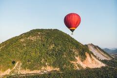 飞行在山和绿色米领域的热气球在Vang Vieng,老挝 库存照片