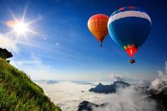飞行在山的五颜六色的热气球 免版税库存图片