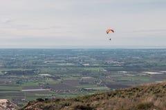 飞行在山的滑翔伞在意大利 免版税库存照片