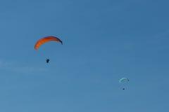 飞行在山的滑翔伞在意大利 库存照片