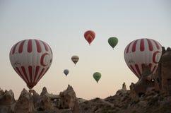 飞行在岩石风景的热空气气球在卡帕多细亚土耳其 库存图片