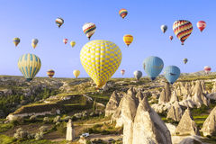 飞行在岩石风景的热空气气球在卡帕多细亚 库存图片