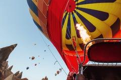飞行在岩石风景的热空气气球在土耳其 cappadocia 免版税库存照片