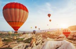 飞行在岩石风景的热空气气球在土耳其 cappadocia 图库摄影