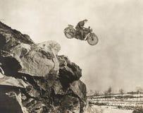 飞行在峭壁的摩托车的替身演员 免版税库存照片