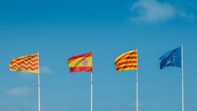 飞行在帆柱的欧盟、加泰罗尼亚语、西班牙人和Tarragonian旗子反对蓝天 免版税库存照片