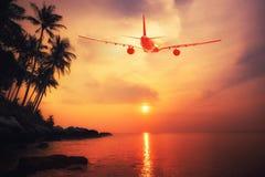 飞行在惊人的热带日落风景的飞机 免版税库存照片