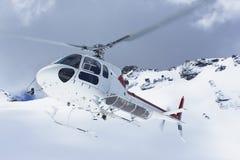 飞行在斯诺伊山峰的直升机 库存照片