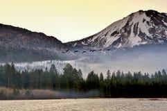 飞行在日出,拉森火山国家公园的加拿大鹅 免版税库存图片