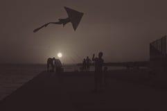 飞行在日落的父亲和儿子剪影一只风筝 图库摄影