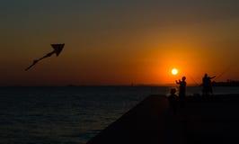 飞行在日落的父亲和儿子剪影一只风筝 库存图片
