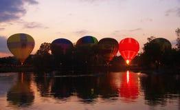 飞行在晚上天空的热空气baloons在湖附近 图库摄影