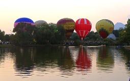 飞行在晚上天空的热空气baloons在湖附近 免版税库存图片