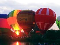 飞行在晚上天空的热空气baloons在湖附近 库存照片