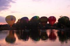 飞行在晚上天空的热空气baloons在湖附近 免版税图库摄影