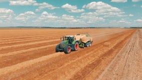 飞行在有做堆麦子夏日的拖车的麦田和联合收割机拖拉机的鸟瞰图 影视素材
