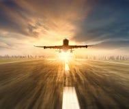 飞行在有城市scape和日落的机场跑道的空中飞机 库存照片