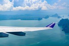 飞行在有多云天空的海的飞机翼 库存图片