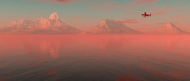 飞行在有山的湖的飞机在天际在日出 免版税库存图片
