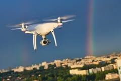 飞行在有数字照相机的城市的寄生虫在彩虹 免版税图库摄影