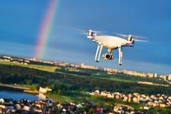 飞行在有数字照相机的城市的寄生虫在彩虹 库存图片