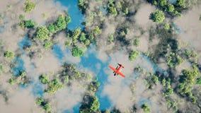 飞行在有湖的森林的红色飞机天线 免版税库存照片