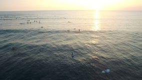 飞行在有等待在水中的许多的海洋冲浪者对日落 影视素材