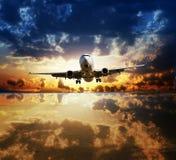 飞行在水表面反射的天空的使飞机降落 免版税库存图片