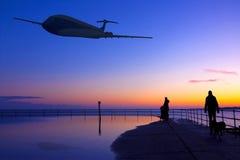飞行在海和土地的飞机在日落 免版税库存照片