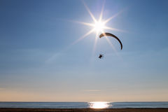 飞行在海和海滩的太阳附近的滑翔伞 免版税库存照片