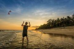 飞行在海滩,人们的人一只风筝学会kitesurfing 库存照片