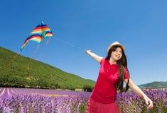 飞行在淡紫色领域的愉快的女孩五颜六色的风筝 图库摄影