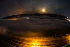 飞行在深夜期间覆盖与月光 虚度上升在与夜城市光的云彩 自然长的快门照片 Sel 库存图片