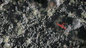飞行在灰色岩石山风景的红色飞机天线 免版税库存图片