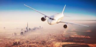 飞行在现代城市的商业飞机 免版税库存图片